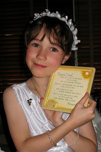 Family and Friends gathered to celebrate Rachel's First Communion at Mimi's Cafe - Rachel displaying her prayer book from Grandma and Grandpa
