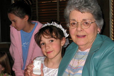 Family and Friends gathered to celebrate Rachel's First Communion at Mimi's Cafe - Rachel displaying her Cross earrings from Grandma and Kathy (Tara in the background)