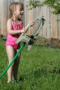 Mae adjusting the sprinkler.