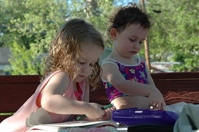 Mary and Tyler take a break from the sprinkler to color in their new coloring books.