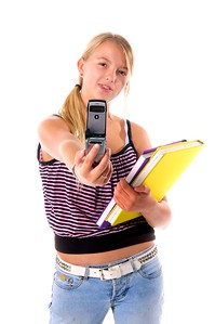 Stylish middle school student with text books taking a photo with a cell phone camera.  Isolated over white
