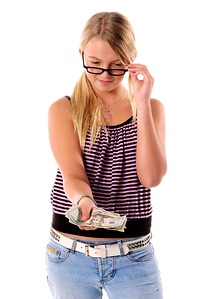 Young girl in cute cloths with a handful of cold hard cash ready to do some Back To School Shopping