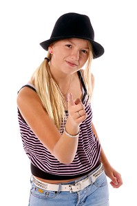 Young girl in cute cloths and a black felt hat pointing mischievously at the camera