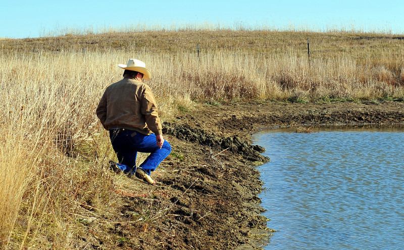 Fred (Afton Williamson's stepfather) kneels down next to the pond.