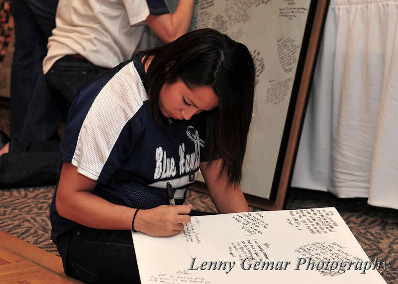 A teammate signs the back of a photo montage.