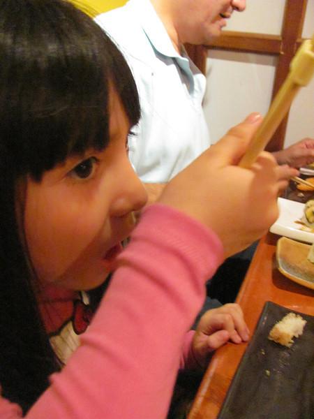 Angela learns to eat with chopsticks.  Angela aprende a comer con palitos.