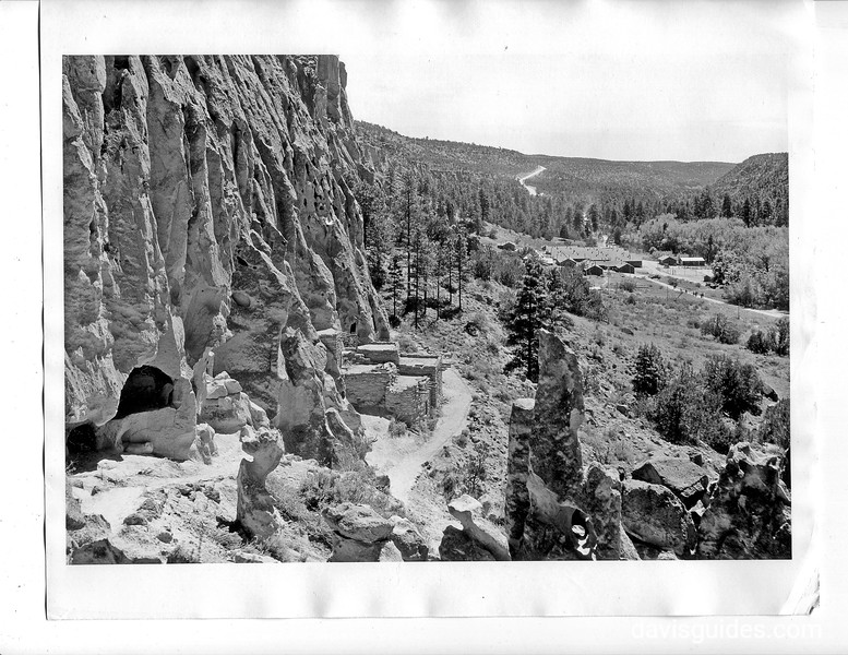 Trail beneath cliff dwellings at Bandelier. CCC camp in the background. 1934