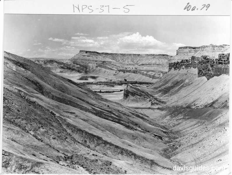 View east from the top of dugway west of Fremont River crossing toward Caineville, Utah, showing tilted strata with horizontal and undisturbed Caineville Mesa beyond. Capitol Reef National Park, 1935