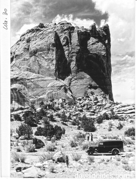 "One of the many high cliffs in Grand Gorge, Capitol Reef National Park, 1935.  Grant's panel truck, the ""Hearse"" in the foreground."