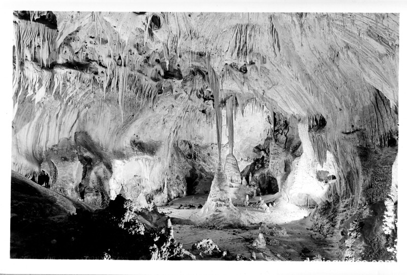 A large stalagmite formation with onyx drapes above it in the King's Palace, Carlsbad Caverns National Park, 1938.