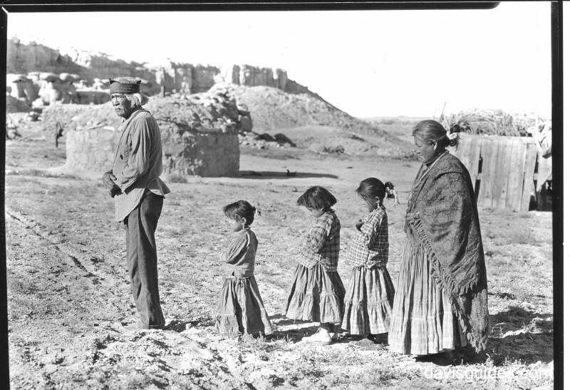 Tomacuto, an old Navajo, with his squaw and grandchildren, Chaco Canyon National Monument (now Chaco Culture National Historical Park), 1929.