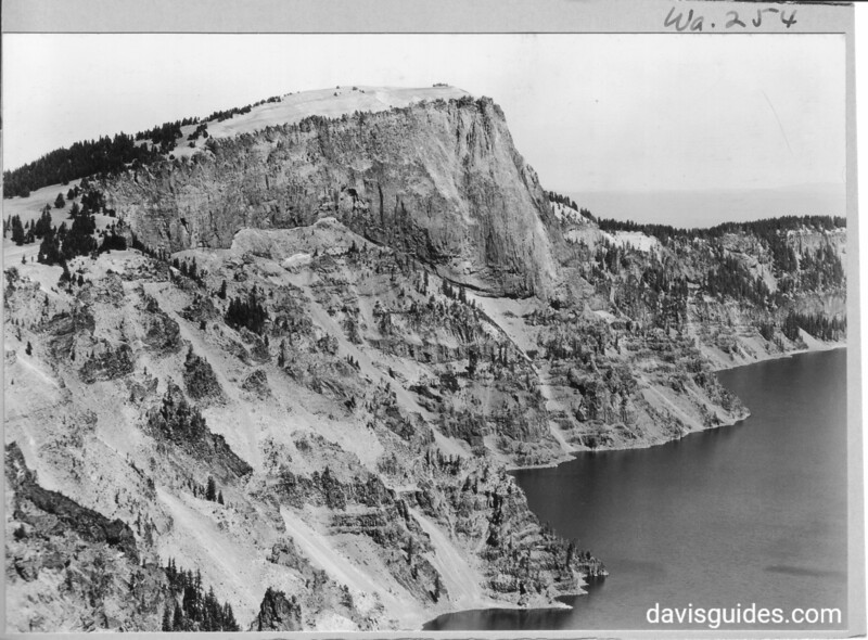 Long focus view of Llao Rock from the slope of Mount Hillman, showing contact line between old glacial valley and lava of Llao Rock.  Image also shows pumice capping, Crater Lake National Park, 1931.
