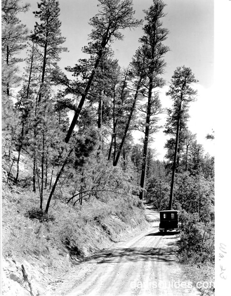 Narrow piece of road on grade leading from bridge to campground.  Gran't panel truck parked on the road.  Devils Tower National Monument, 1933.