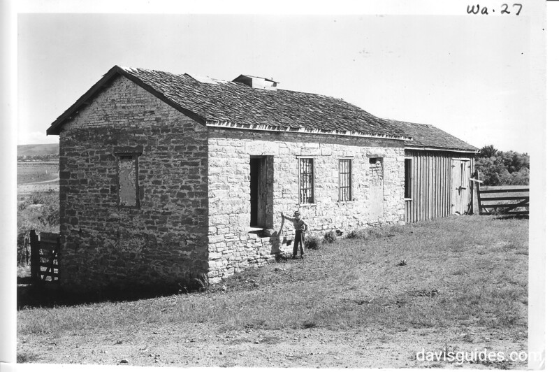 The jail or guardhouse at old Fort Laramie as seen from the west or parade ground side. Master Frederick Wells of Laramie in the picture. Fort Laramie National Historic Site, 1932.