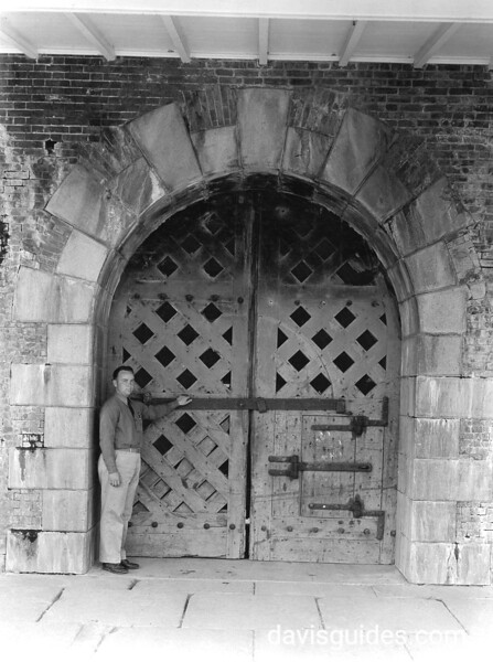Park ranger by old wooden door inside the sally port. The door is on the inside of the throat, or gorge, of the fort facing the parade ground. Fort Pulaski National Monument, 1937.