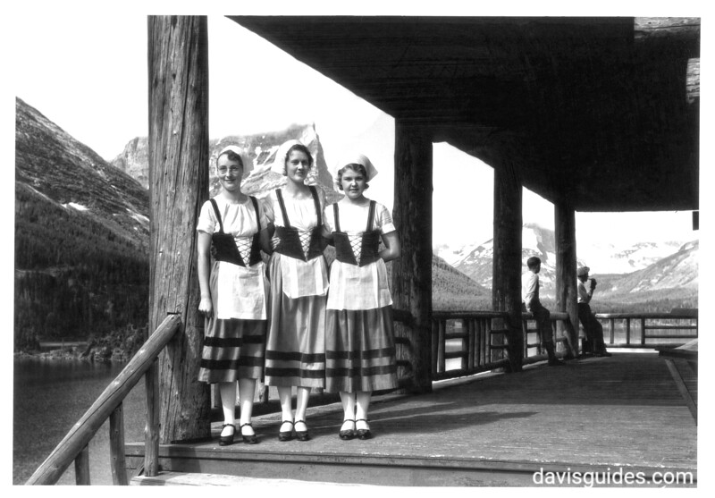 Servers in Swiss costumes on the verandah of Going to the Sun Chalets, Upper St. Marys Lake, Glacier National Park, 1933.