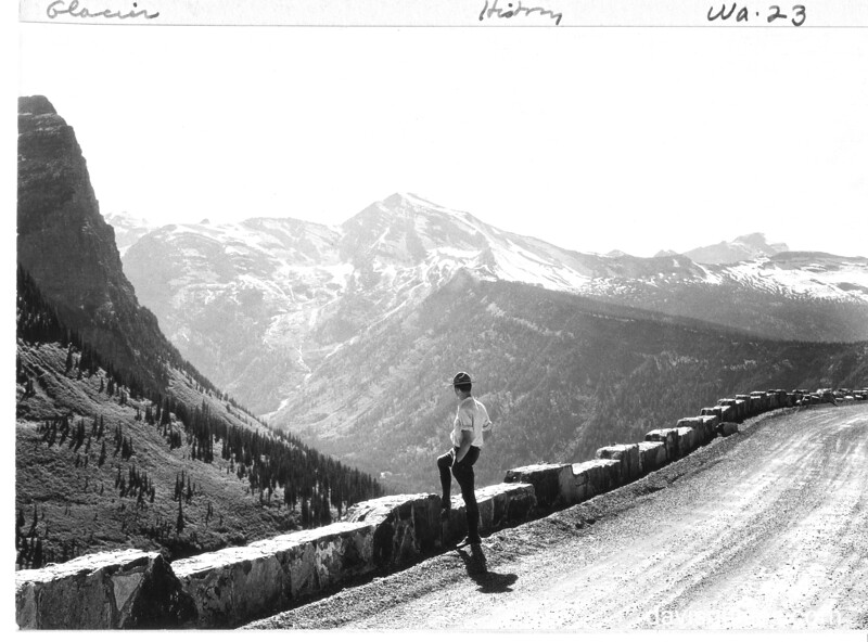 Stone parapet along the Transmountain Highway (Going to the Sun Road), Lake McDonald side. The ranger in the photograph shows the height of the parapet. Glacier National Park, 1932.