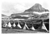 Blackfoot teepees (tipis) near the summit of Logan Pass and beneath Mount Reynolds, in preparation for the dedication ceremony of the Going to the Sun Road. Glacier National Park, July 14, 1933.