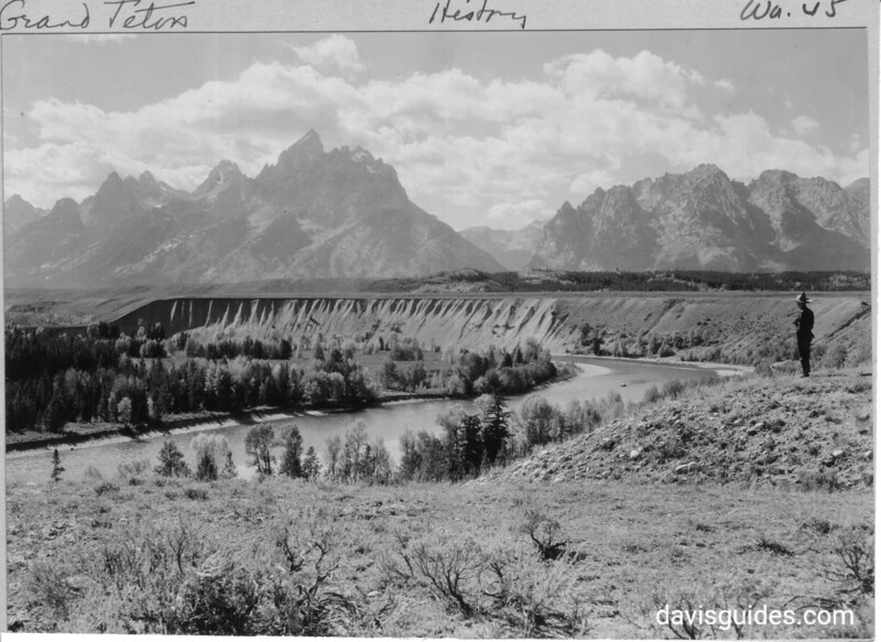 The three Tetons and Mount St. John from Deadman's Bar. Snake River in foreground with Karl Kent, proprietor of Jenny Lake Inn. Grand Teton National Park, 1930.