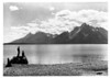 Jackson Lake and the Tetons from the small island out from CCC camp No. 2. Enrollees Ray Ickes and Ned Munn are on the rocks in the foreground. Grand Teton National Park, 1933.