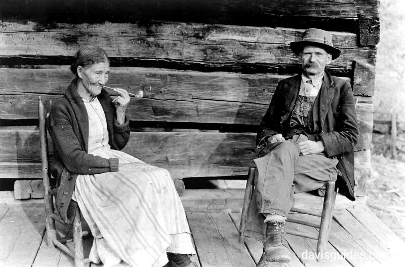 Aunt Sophie and Uncle Tom Campbell are seated on the front porch of their rustic log cabin near Gatlinburg, Tennessee. Planned Great Smoky Mountains National Park, 1931.
