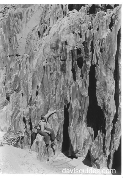 A visitor examines the potholes in the granite of north wall at Separation Rapids. Lake Mead National Recreation Area, 1939.