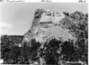 Heads of Washington and Jefferson. To the right, men are working on Lincoln. Mount Rushmore National Memorial, 1936.