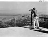 Clifford Bond looking through telescope at Mount Tamalpais Inn toward San Francisco. Muir Woods National Monument, 1933.