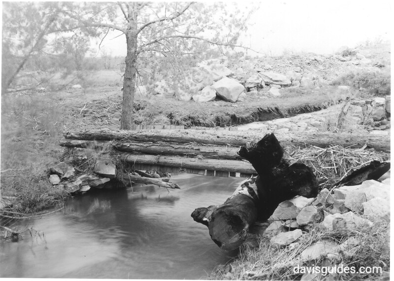 Foot bridge over creek above the falls, near railroad tracks. Note large logs carried downstream. The result of a cloudburst on Sunday, May 24, 1953. Pipestone National Monument, 1953.