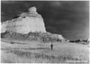 The spectacular bluff on the north side of Mitchell Pass. Tom Green of Scotts Bluff, Nebraska, stands on the site of William H. Jackson's Bull Train Camp of August 3, 1866. Scotts Bluff National Monument, 1938.