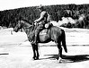 George Grant on horseback, preparing for a photography trip in the backcountry. Yellowstone National Park, 1933.