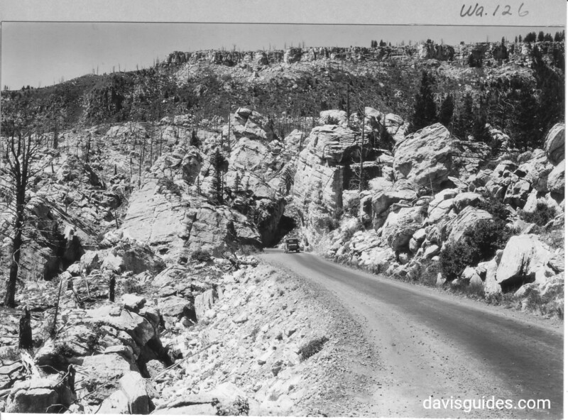 Entering the Hoodoos at Silver Gate. Note light colored travertine crust on Terrace Mountains on skyline resting on brownish rhyolite rocks beneath. Yellowstone National Park, 1931.