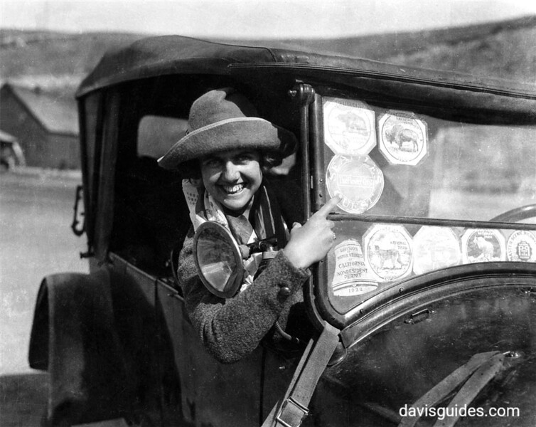 Approximate Year: 1922<br /> Park: Yellowstone National Park<br /> Photographer: Unknown <br /> Description: Park Visitor showing off her park stickers (indicating that entrance fees were paid at various National Parks). [While uncredited, the photographer is believed to have been George Grant],