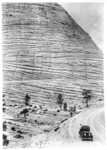View along Mount Carmel Highway showing crossbedding of sandstone and weathered surface fractures. George Grant's NPS photographic car in the foreground. Zion National Park, 1929.