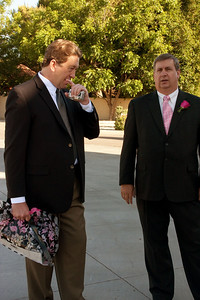 Doug and bride's stepfather chat in the driveway while photos take place.