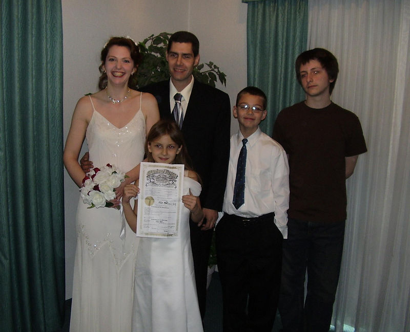 The happy couple; Kyra, holding the marriage certificate; Tyler, and David.