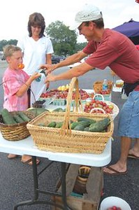 """The Downtown Farmers Market kicked off the 2007 season the evening of Monday June 11, beginning at 5 p.m.   Above, 10-year-old Austin Newman helps his dad David pack up goodies purchased by a devoted customer at The Downtown Farmer's Market.  Newman, one of several vendors who set up along the roadway beside United Banks Downtown Branch, has been coming to the market since it's beginning. &#8220I started helping Dad out with this first,"""" said Newman, who has been selling their homegrown produce and Christmas trees for 15 years. &#8220When the market started down here, Dad would come up on his own and after some time I decided to join him. Now my son comes with me. It's definitely a family affair."""" Newman's bounty of garden treats left nothing to the imagination. He says the garden, which is close to four acres, is doing as well as expected and last Friday's rainfall was a welcome sight. &#8220Today we have Silver Princess corn, cucumbers, squash and some fresh fruit. As the season progresses and if the rain continues we will have just about anything anyone could ask for."""" Don't forget, the Downtown Farmers Market is available to the public every Wednesday morning from 8 a.m. until noon and Monday evenings beginning at 5 p.m. now until the first week of October. Vendors will be set up behind the downtown branch of United Bank."""