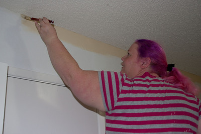 Sally painting the edge of a tan wall.