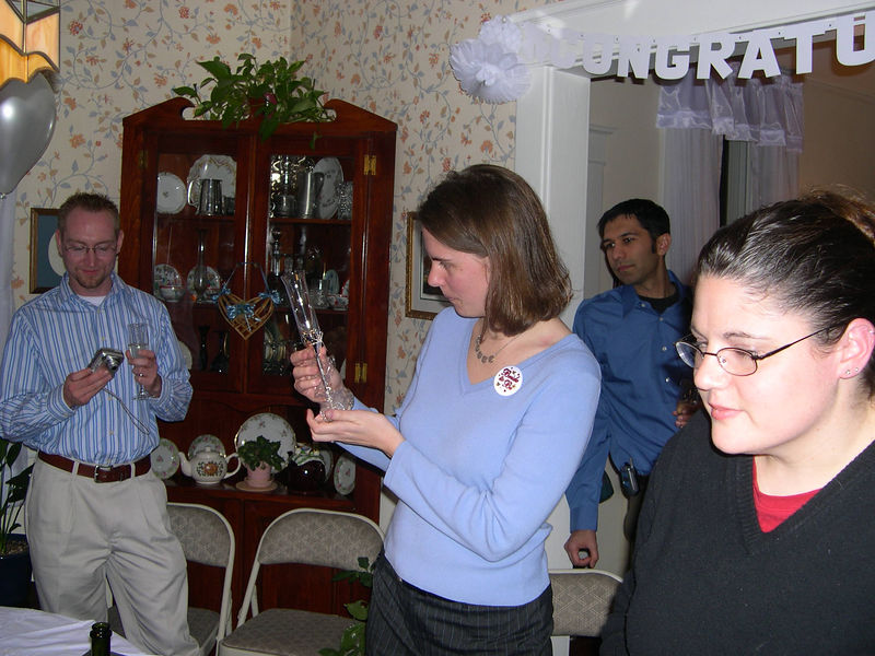 Liz admires a champagne flute to celebrate her engagement.  Her friend, Susan, is in the foreground, with Jason and Neil looking on.
