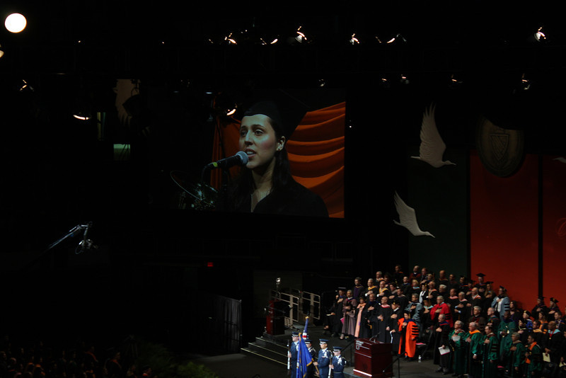 Woman graduating from music program singing the national anthem.
