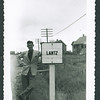 Lloyd Lantz by sign for Lantz, probably Nova Scotia.