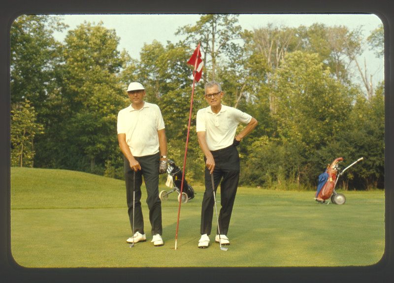 Man and Lloyd Lantz on golf green.