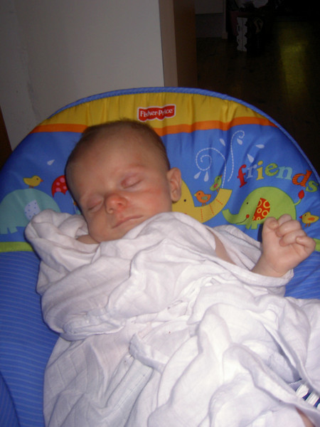 Sleeping in his new bouncer, but with the Baby Power salute.
