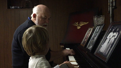 Luca playing piano with Uncle George.
