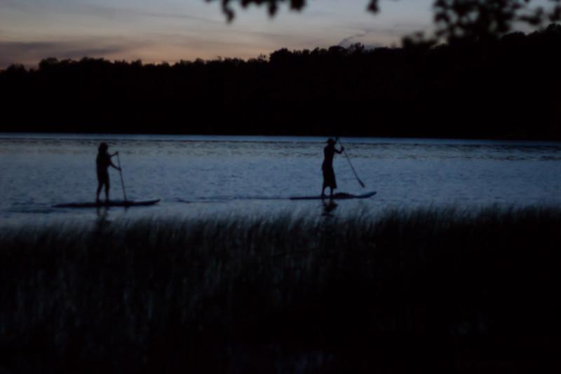 Becca and Jen paddleboarding at night.