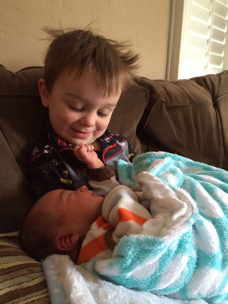 Max loves holding his new baby brother