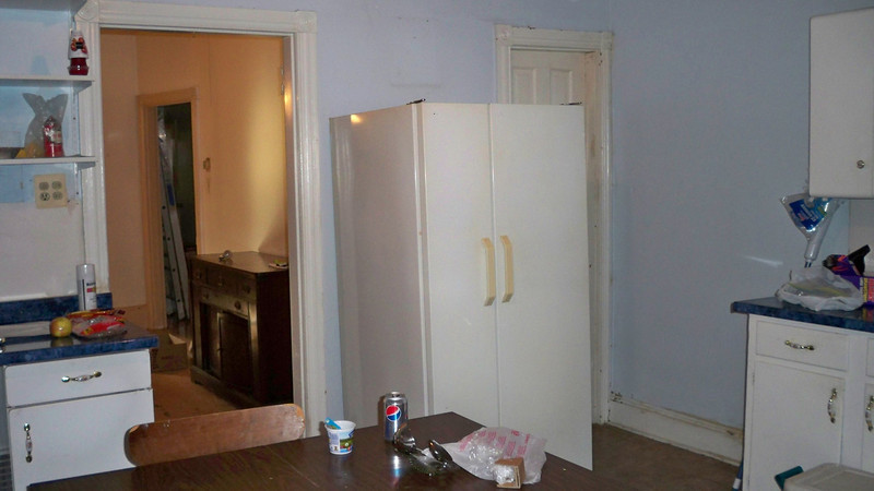 Door to Dining room and basement entrance to right of fridge.