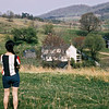 "April 1966:  Judy on hill overlooking farmhouse.  This view is now partially obscured by trees and bushes that have since grown.  All of the outbuildings shown in the photo are now gone.  The structure closest to the camera with the brick chimney (""Conrad's birthplace"" in the event he was ever to run for political office) was the smokehouse.  Only the chimney remains today."