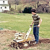 April 1977:  Rototilling the garden.  To the back, Conrad's birthplace has not yet wholly disintegrated.