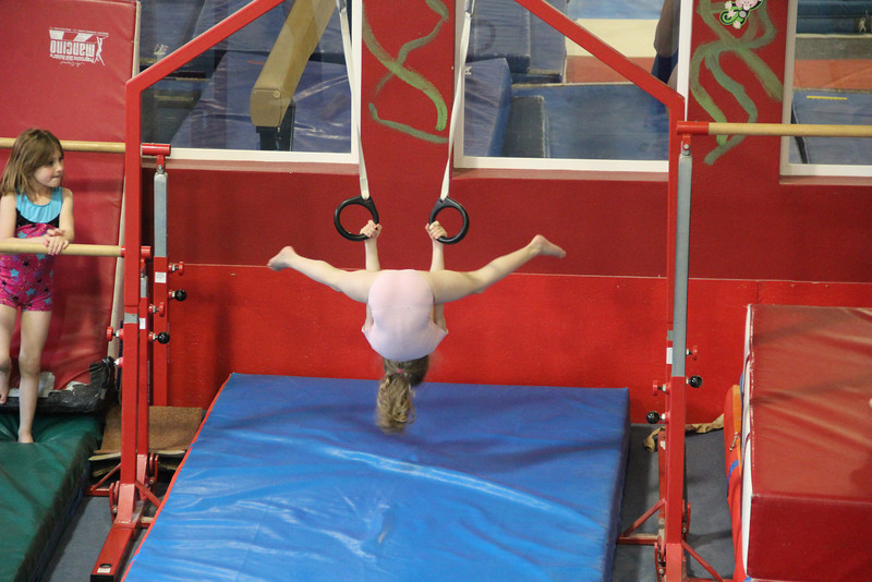 Norah practicing straddles on the rings.